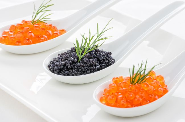 19292047 - red and black caviar on porcelain spoons
